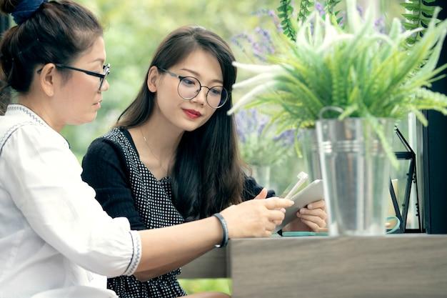 Deux, femme asiatique, à, téléphone main, conversation, dans, maison, salle de séjour, à, bonheur, figure