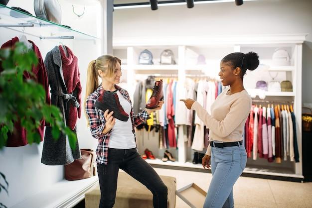 Deux femmes achètent des vêtements et des chaussures. accro du shopping dans un magasin de vêtements, mode de vie de consommation, mode