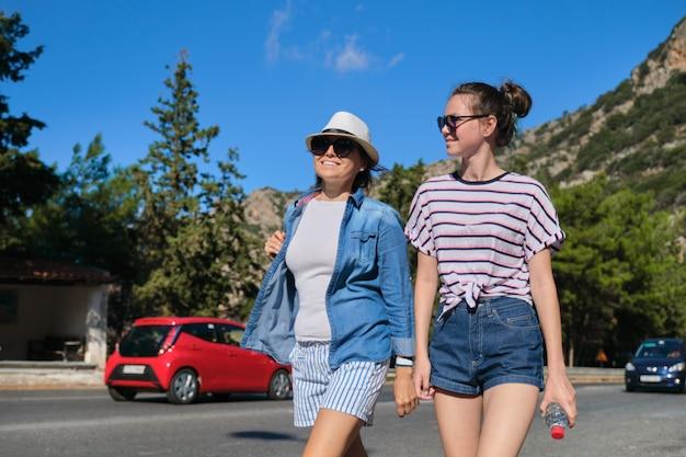 Deux femmes adolescentes mère et fille marchant sur une journée d'été ensoleillée sur la route de montagne. tourisme, excursions, voyages, vacances en famille