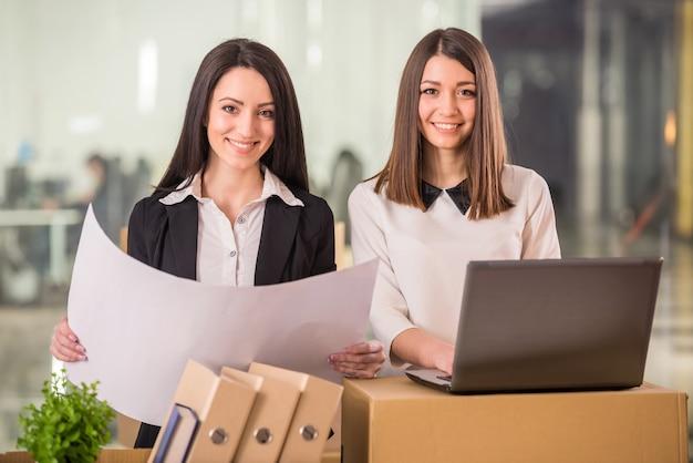 Deux femmes d'affaires adultes préparant leur nouveau bureau.