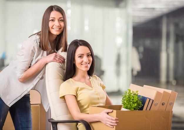 Deux femmes d'affaires adultes s'installant dans un nouveau bureau.
