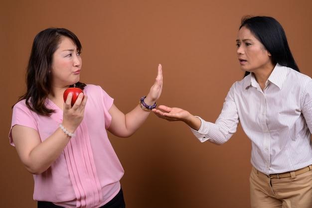 Deux femmes d'affaires asiatiques matures ensemble contre un mur marron