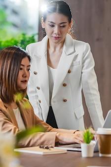 Deux femmes d'affaires asiatiques travaillant avec l'entreprise partenaire via un ordinateur portable technologique en moder