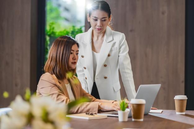 Deux femmes d'affaires asiatiques travaillant avec l'entreprise partenaire via un ordinateur portable technologique