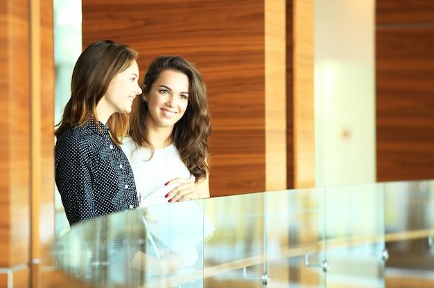 Deux femmes d'affaires ayant une réunion informelle dans un bureau moderne.