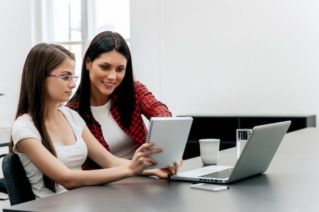 Deux femmes d'affaires consultant un rapport ensemble sur un bureau au bureau.