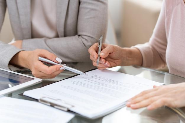 Deux femmes d'affaires consultent ou discutent des termes du contrat avec leurs mains sur le document