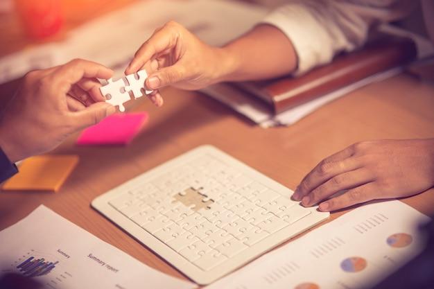 Deux femmes d'affaires essayant de connecter une pièce de puzzle
