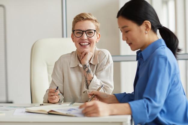 Deux femmes d'affaires joyeuses appréciant le travail au bureau, copiez l'espace