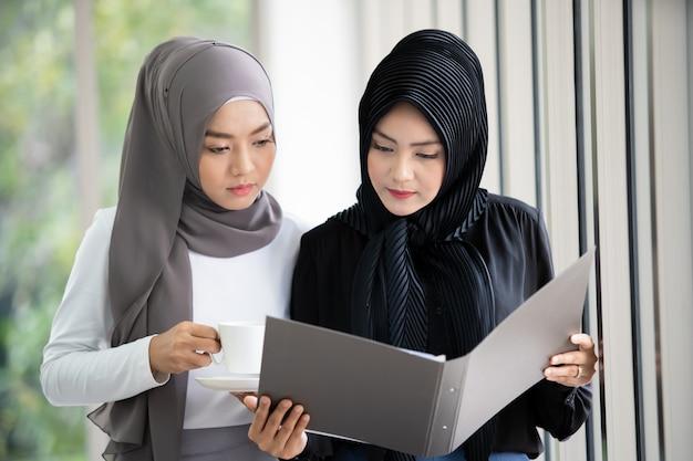 Deux femmes d'affaires musulmanes asiatiques discutant et travaillant ensemble au bureau