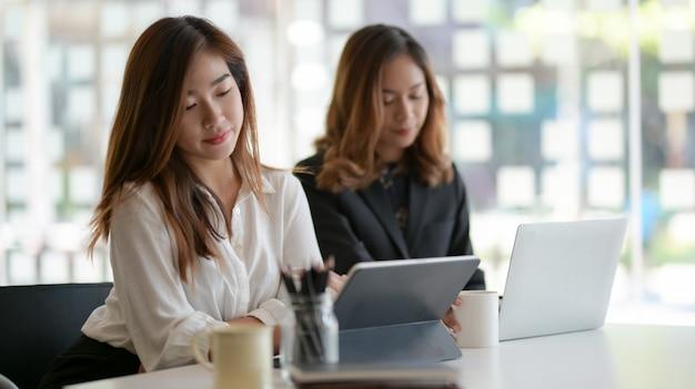Deux femmes d'affaires professionnelles travaillant ensemble sur le projet dans un bureau moderne