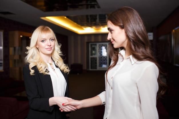 Deux femmes d'affaires se serrant la main dans un bureau moderne