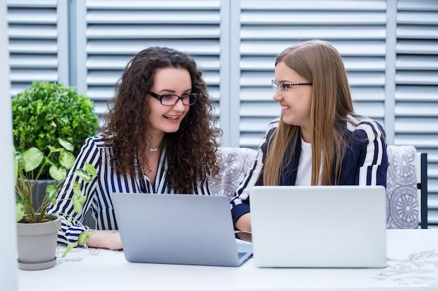 Deux femmes d'affaires sont assises dans un café lumineux avec un ordinateur portable et des papiers d'affaires et parlent avec des gens sérieux. les employés de bureau sont assis sur des pauses-café et travaillent. réunion d'affaires dans un café