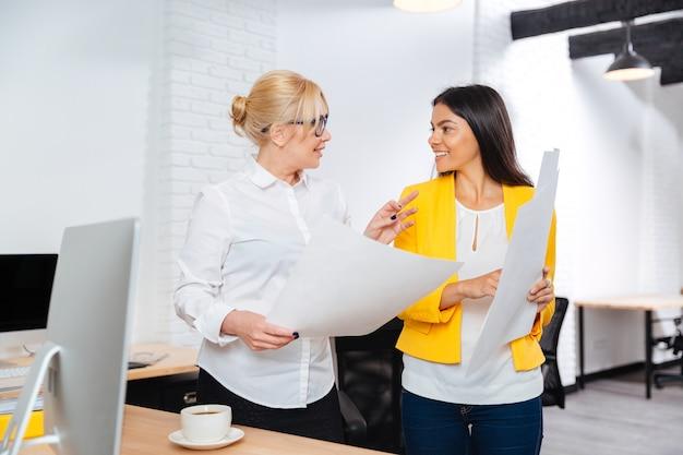 Deux femmes d'affaires souriantes ayant une réunion au bureau