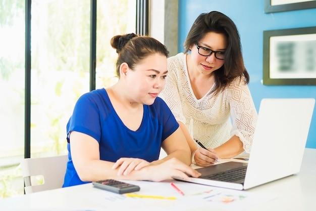 Deux femmes d'affaires travaillent avec un ordinateur au bureau