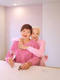 Deux femmes âgées élégantes en chandails roses assis avec des verres à vin au bar en train de parler