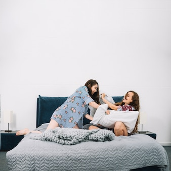 Deux femmes amis oreiller se battre sur le lit