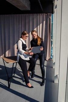 Deux femmes architectes à succès parlent d'un projet commun tout en se tenant à la fenêtre avec un ordinateur portable. de jeunes femmes économistes vêtues de tenues formelles parlant pendant une pause du travail