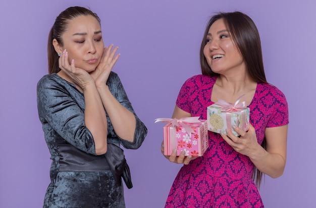Deux femmes asiatiques célébrant la journée internationale de la femme, femme confuse regardant sa meilleure amie souriante