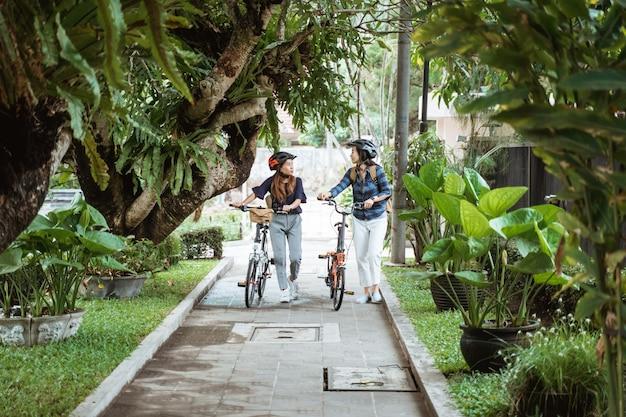 Deux femmes asiatiques discutant et marchant tout en se promenant avec des vélos pliants