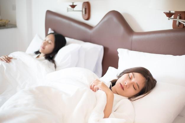 Deux femmes asiatiques dorment sur le lit. thème des personnes et des modes de vie.