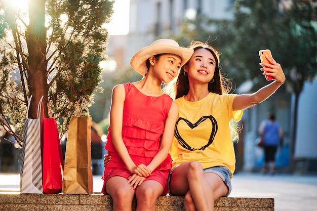 Deux femmes asiatiques faisant du shopping et prenant un selfie à l'extérieur