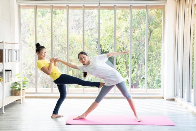 Deux femmes asiatiques heureuses dans des poses de yoga en studio de yoga avec scène de réglage de la lumière naturelle / concept d'exercice / pratique du yoga / espace copie / studio de yoga
