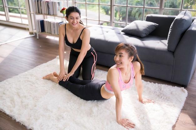 Deux femmes asiatiques s'entraînant au fitness et au yoga à la maison