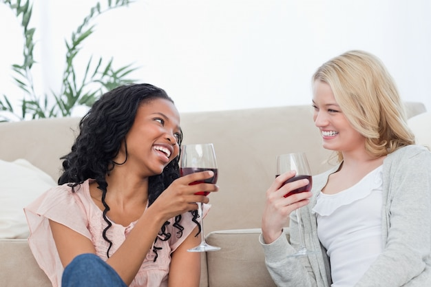Deux femmes assises sur le sol parlent et boivent du vin