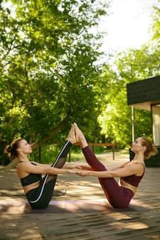 Deux femmes au corps mince faisant de l'exercice ensemble sur une formation de yoga en groupe en journée ensoleillée dans le parc. méditation, cours de fitness en plein air