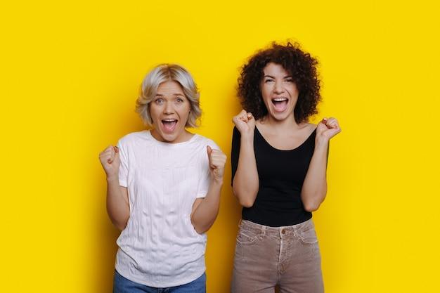 Deux femmes aux cheveux bouclés surpris crient