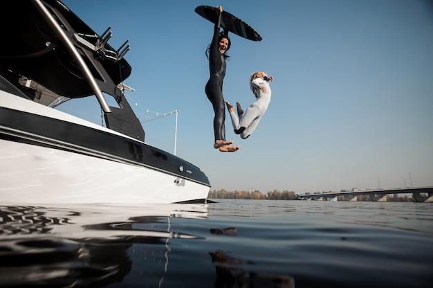 Deux femmes blondes et brunes sautant à la rivière avec wakeboard au bord de la rivière