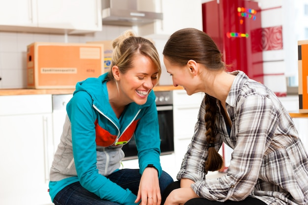 Deux femmes avec une boîte de déménagement dans sa maison