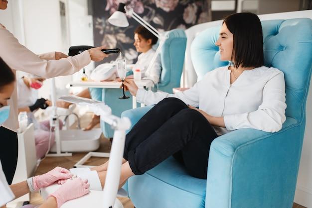 Deux femmes avec champagne, procédure de pédicure dans un salon de beauté.