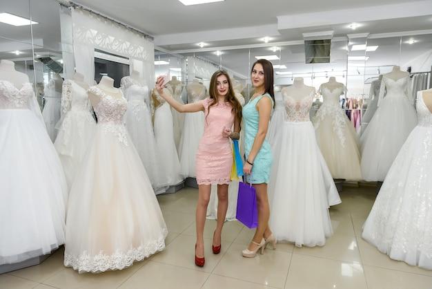 Deux femmes choisissant la robe de mariée en boutique