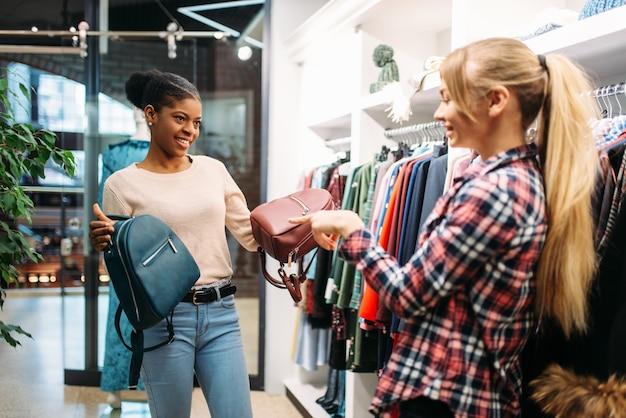 Deux femmes choisissant des sacs en boutique. accro du shopping dans un magasin de vêtements, mode de vie de consommation, mode