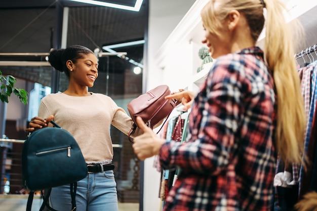 Deux femmes choisissant des sacs en boutique