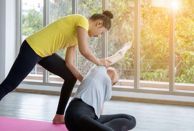 Deux femmes en classe, exercice de relaxation ou cours de yoga après l'entraînement près du studio de la fenêtre