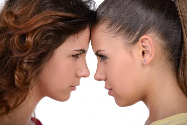 Deux femmes en colère se tiennent les bras croisés.