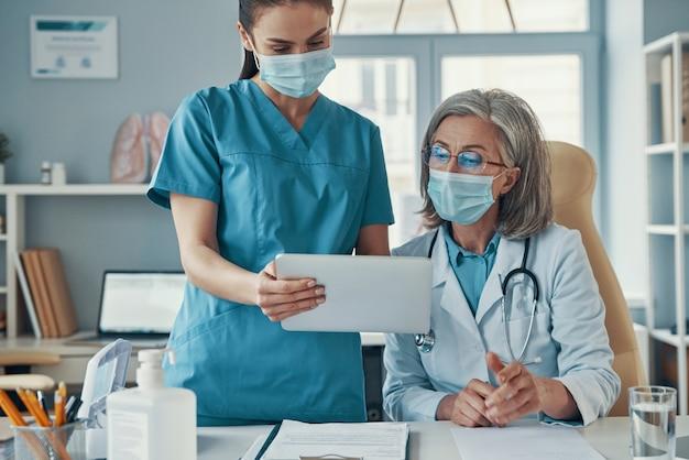 Deux femmes collègues en uniforme médical et masques de protection parlant et utilisant une tablette numérique tout en travaillant à l'hôpital