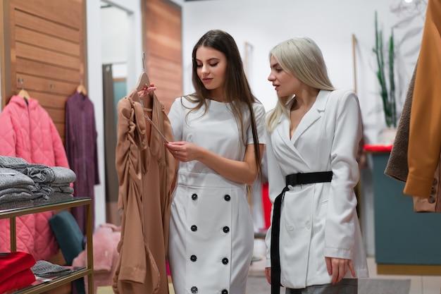 Deux femmes dans une boutique de mode choisissent une robe un styliste professionnel aide les clients à choisir des vêtements. saison vacances shopping remises vente deux copines caucasiennes à pied centre commercial