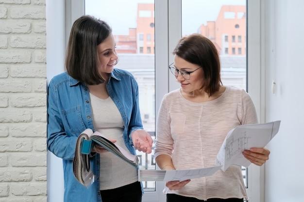 Deux femmes designers travaillant avec des échantillons de tissus pour l'intérieur. choix des tissus pour rideaux, tissus d'ameublement, calcul du coût