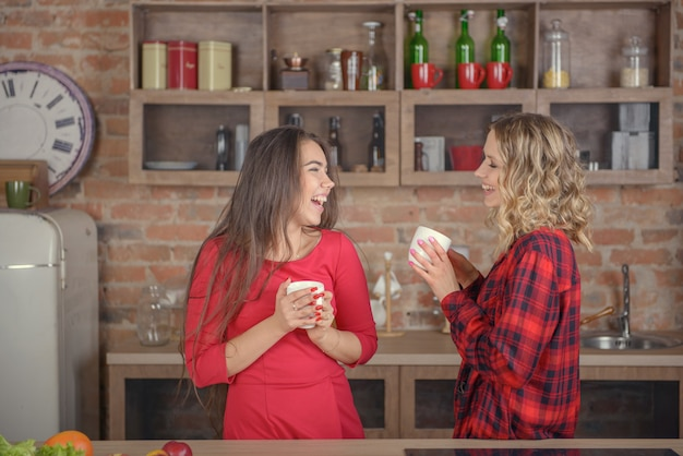 Deux Femmes Discutant Autour D'une Tasse De Café Dans La Cuisine Photo Premium