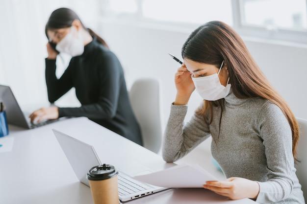 Deux femmes doivent porter des masques pendant les heures de travail pour rester en sécurité pendant les épidémies