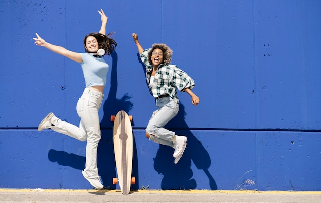 Deux femmes drôles sautant ensemble sur un mur bleu, écoutent des écouteurs de musique, planche à roulettes