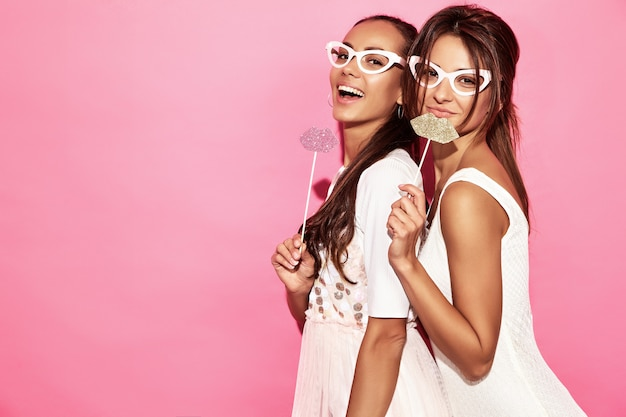 Deux femmes drôles surpris dans des verres en papier et de grosses lèvres sur bâton. concept intelligent et beauté. jeunes mannequins joyeux prêts pour la fête. femmes isolées sur mur rose. femme positive