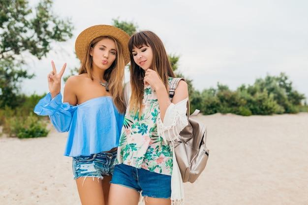 Deux femmes élégantes assez souriantes en vacances d'été sur la plage tropicale, des amis voyagent ensemble