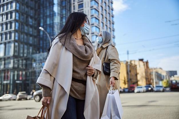 Deux femmes élégantes portant des masques médicaux debout dans la rue
