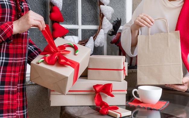 Deux femmes emballant des cadeaux à la veille des fêtes de noël et du nouvel an.