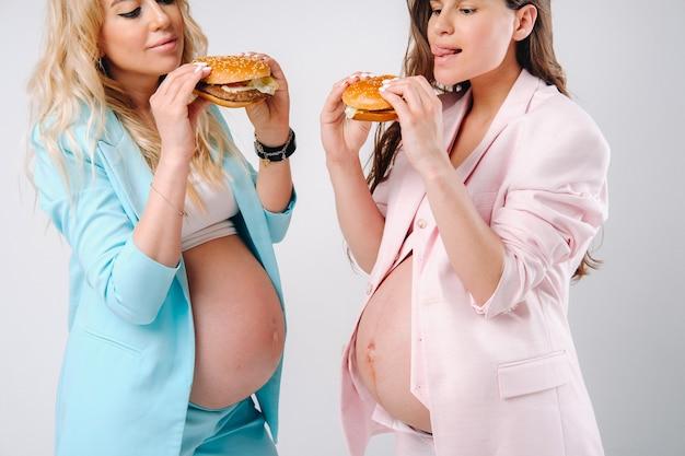 Deux femmes enceintes en costume avec des hamburgers à la main sur fond gris.